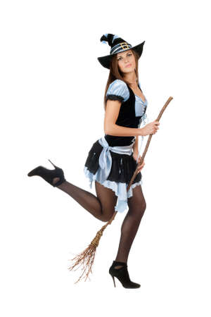 Playful young woman with a besom wearing costume witch photo