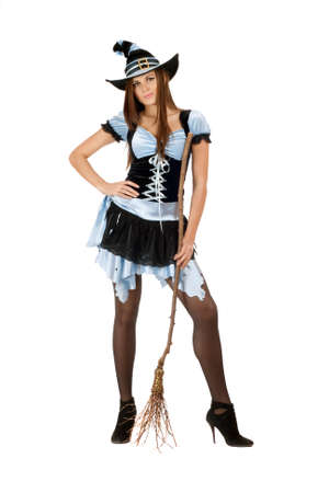 Charming young woman with a besom wearing costume witch photo