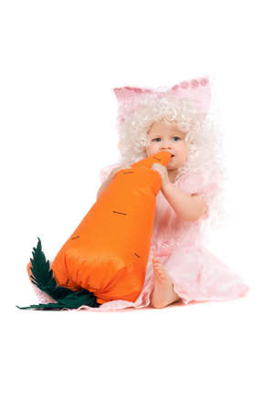 Baby girl plays with a carrot. Isolated photo