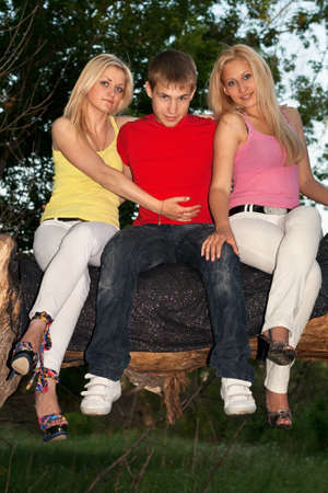 Two playful blonde and young man sitting on a tree branch Stock Photo