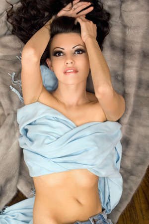 Passionate sexy young woman lying on grey fur photo