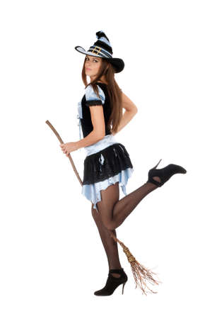 Playful beautiful young woman with a besom wearing costume witch photo