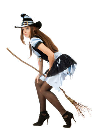 Beautiful young woman with a besom wearing costume witch