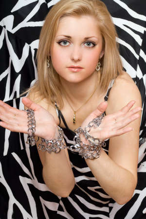 Sensual beautiful blonde stretches out her hands in chains photo
