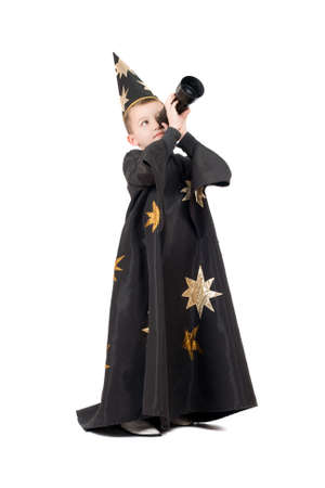 Boy dressed as astrologer looking through a telescope photo