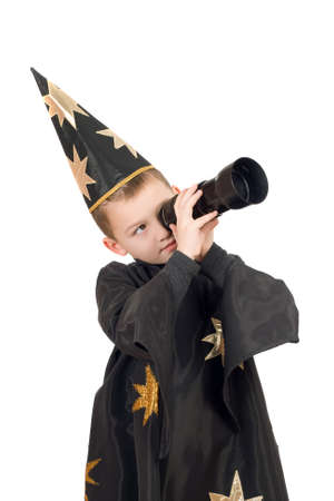 Boy dressed as astrologer looking through a telescope. Isolated photo