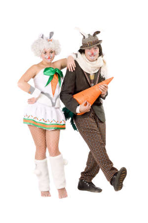Funny couple with carrot dressed as rabbits. Isolated on white photo