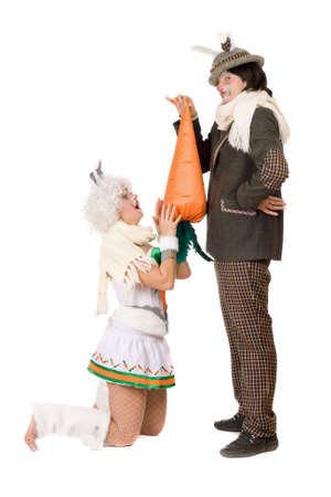 Funny young couple with carrot dressed as rabbits. Isolated on white photo