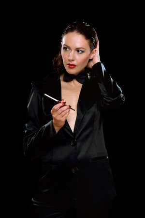 Elegant young woman with cigarette wearing a black suit photo