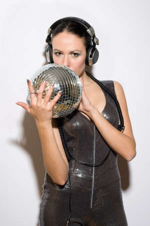 Portrait of pretty young brunette in headphones with a mirror ball photo