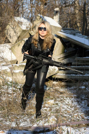 Pretty young blonde with a gun outdoors photo