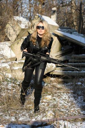 ljuddämparen: Söt ung blondin med en pistol utomhus Stockfoto