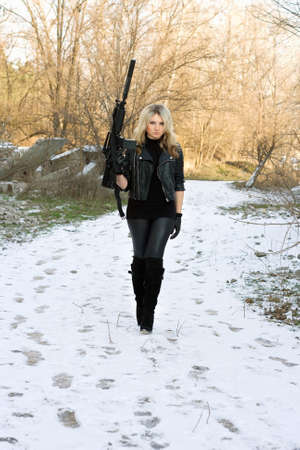 Beautiful young blonde with a gun outdoors photo