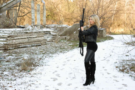 Nice young blonde with a gun outdoors photo