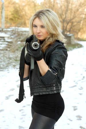 ljuddämparen: Porträtt av trevlig ung blondin med en pistol utomhus