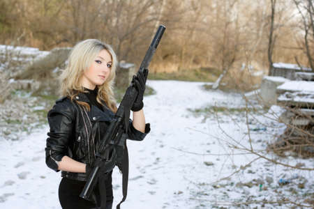 silencer: Portrait of beautiful young blonde with a gun outdoors Stock Photo