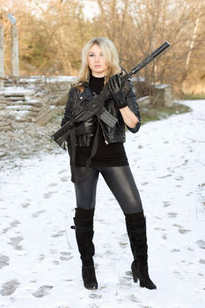 Sexy young blonde with a gun outdoors photo