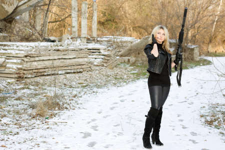 Nice young woman with a gun outdoors photo