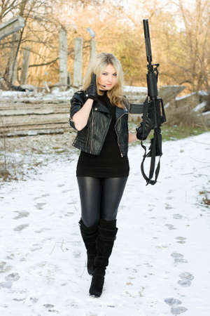 the silencer: Sexy young woman with a gun outdoors Stock Photo