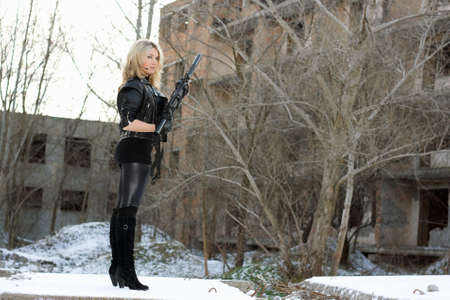 Young sexy woman with a gun outdoors photo