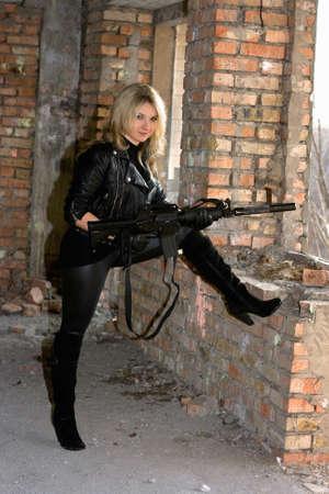 ljuddämparen: Ung sexig kvinna klädd i svart med en pistol Stockfoto