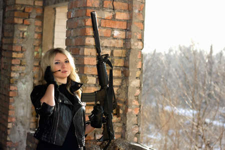 Portrait of young sexy woman with a gun photo