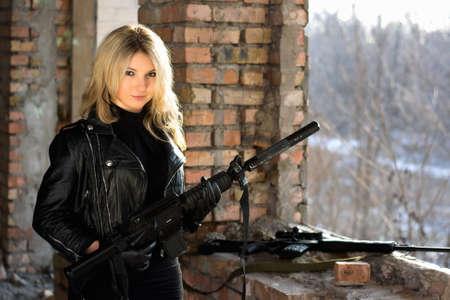 ljuddämparen: Porträtt av ung trevlig kvinna med en pistol Stockfoto