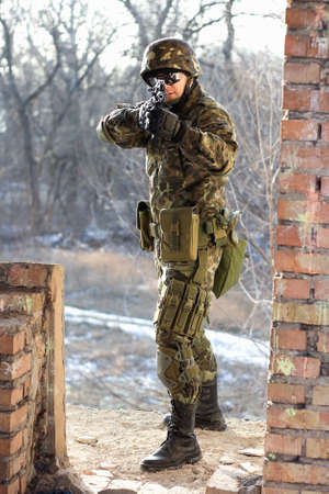 Soldier near wall with a gun in his hands photo