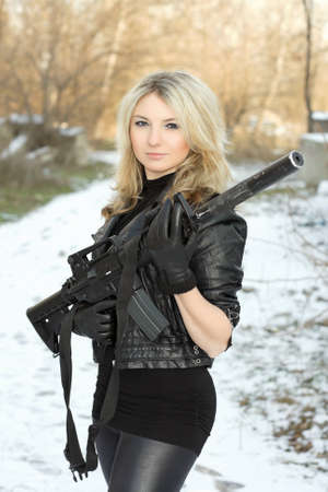 Portrait of pretty young blonde with a gun outdoors photo