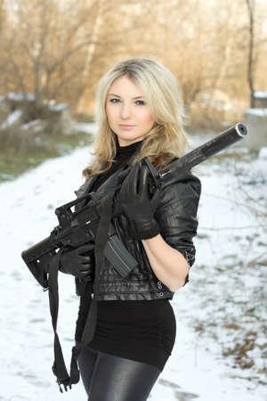 mujer con pistola: Retrato de joven rubia bonita con un aire libre de armas de fuego