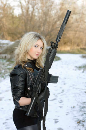 Portrait of perfect young blonde with a gun outdoors photo