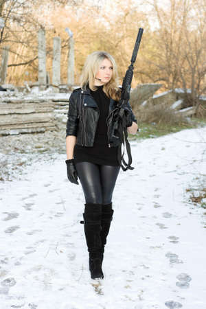Pretty young woman with a gun outdoors photo