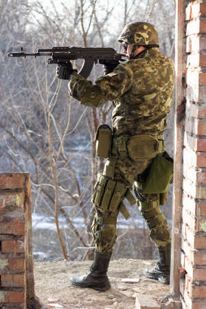 Soldier standing near wall with a gun in his hands photo