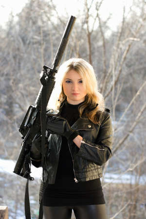 Portrait of perfect young blonde with a gun photo