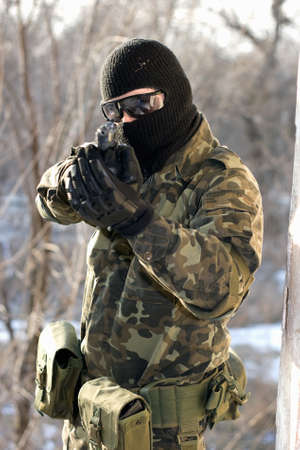 Portrait of soldier with a handgun in his hands photo