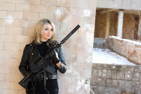 the silencer: Portrait of young pretty woman with a gun
