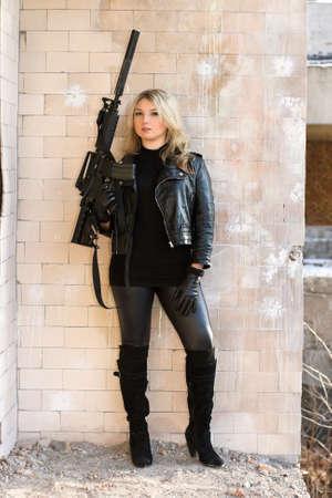 ljuddämparen: Porträtt av ung vacker kvinna med en pistol Stockfoto
