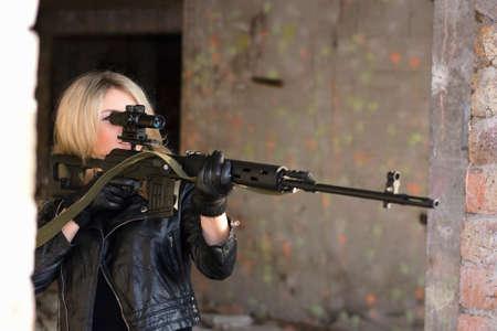 ljuddämparen: Porträtt av ung kvinna med ett prickskyttegevär