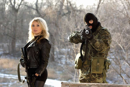 Soldier and young blonde armed with rifles Stock Photo