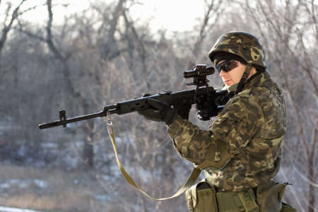Soldier with a sniper rifle in his hands photo