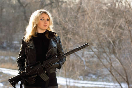airsoft gun: Portrait of attractive young blonde with a gun