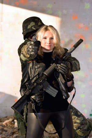 airsoft gun: Soldier with a gun and girl with rifle Stock Photo