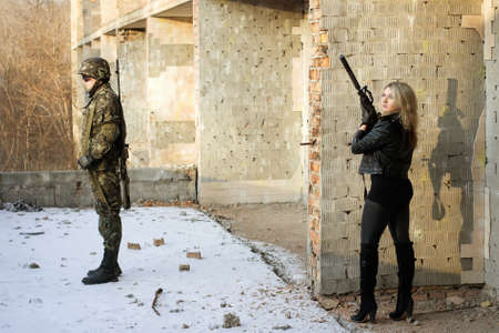 Strong girl aim at a back of soldier photo