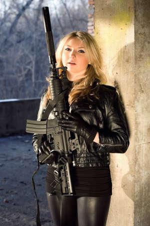 silencer: Hot young woman in leather jacket holding a rifle Stock Photo