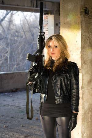 ljuddämparen: Ung kvinna med ett gevär i övergivna hus Stockfoto