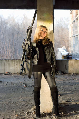 Dangerous young woman with rifle leaned against  the wall photo
