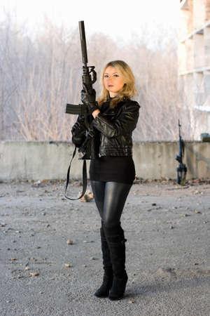 ljuddämparen: Flicka som håller ett gevär i övergivna hus Stockfoto