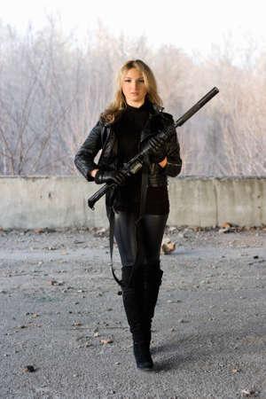 ljuddämparen: Nätt flicka som håller en pistol i försummade byggnaden Stockfoto