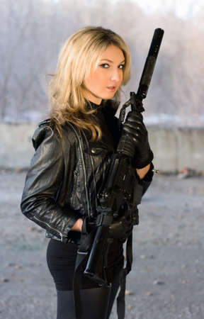 Pretty young woman with curious eyes holding a gun photo
