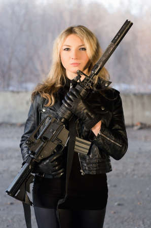 Armed beautiful young woman with a rifle in neglected house photo